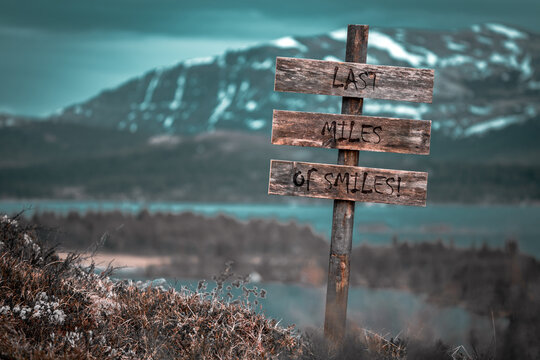 last miles of smiles text quote engraved on wooden signpost outdoors in landscape looking polluted and apocalyptic.