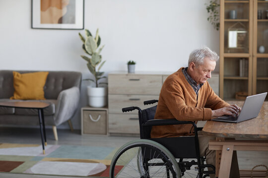 Side view portrait of senior man in wheelchair using laptop while working at desk in home interior, copy space
