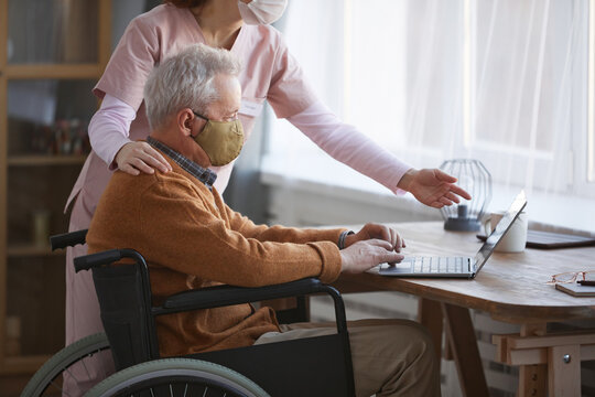 Cropped side view portrait of senior man in wheelchair using computer with nurse assisting him, both wearing masks, copy space