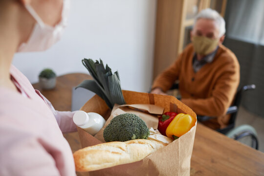 Close up of young woman bringing groceries to senior man in wheelchair, food delivery service concept, copy space