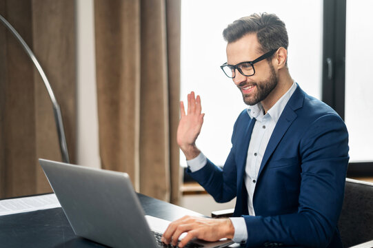 Video call concept, young good-looking man wearing suit and glasses is using a laptop for video connection with family, remote meeting, say hi, looking at the webcam, glad to see, in stylish office