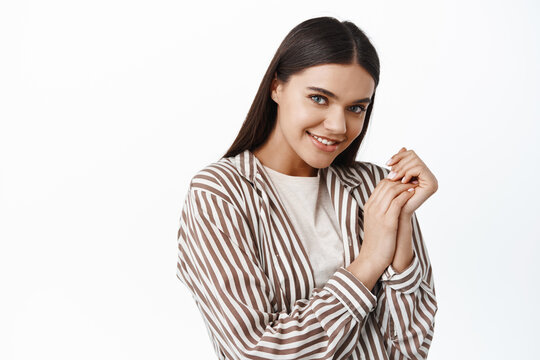 Image of beautiful and coquettish young brunette woman, gazing at camera with love and tenderness, making eye contact, flirting, standing over white background