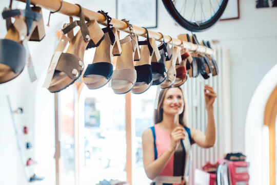 Woman looking at shoes dangling from the ceiling in store