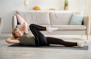Fit senior woman doing abs exercises on yoga mat indoors, empty space. Strength training concept