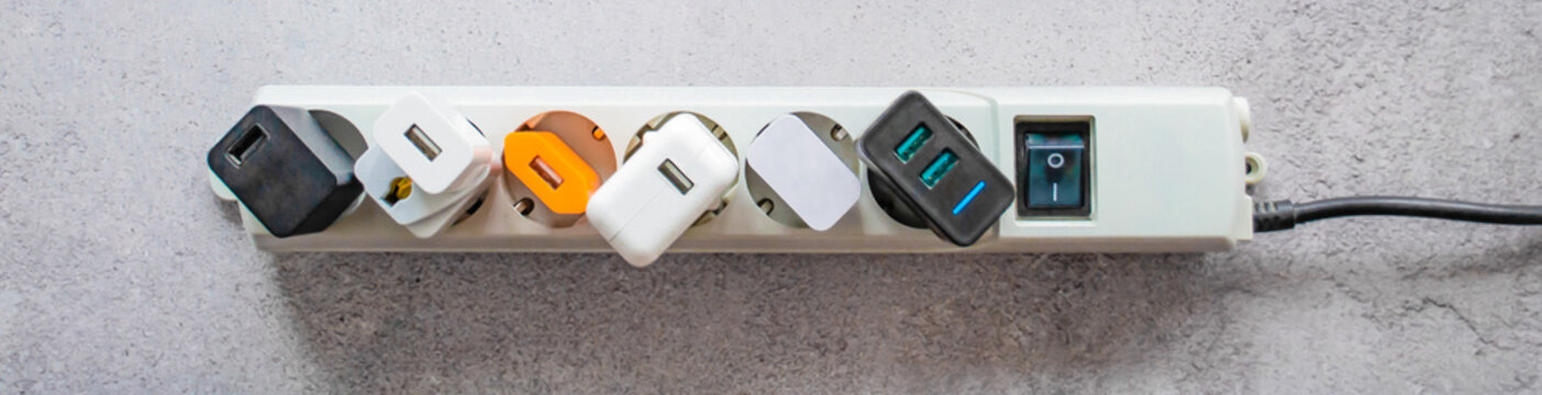 Banner running modern extension power strip with many different USB DC output ports. Cracked concrete background. Copy space