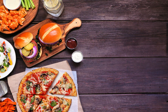 Healthy plant based fast food side border. Above view over a dark wood background. Table scene with cauliflower crust pizza, bean burgers and vegetarian sides. Copy space.