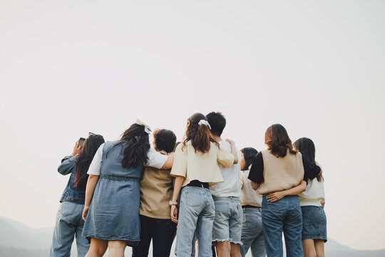 Picture from behind view of groups of friends embrace each other together. Concept for kindness support of people having fun with diversity millenials of gen z.