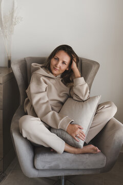 Woman dressed in comfy loungewear of grey color sitting in a cozy and comfortable armchair. Casual outfit. Home clothing. Female's portrait
