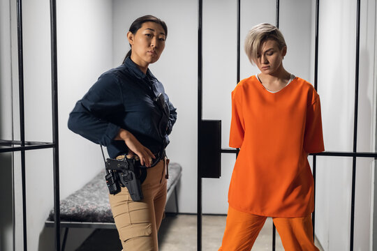 Shooting a movie about a women's prison. Backstage. Asian warden and a criminal girl in a yellow robe on the background of a prison cell