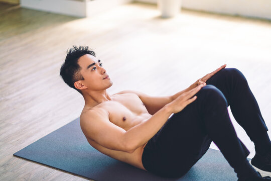 Muscular Asian young man doing  exercises on floor at home