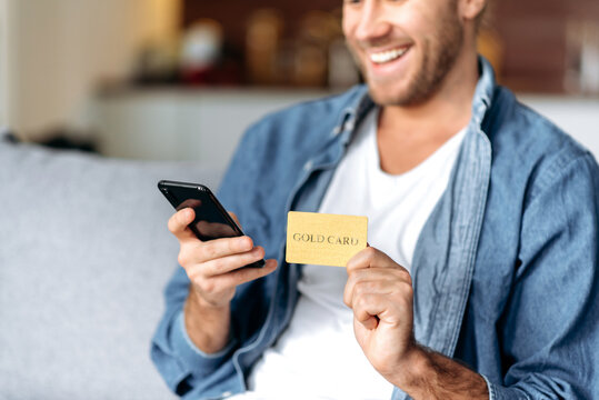 A credit card and smartphone in male hands. Joyful caucasian young man in defocus looks at the phone screen, shopping online, using banking card. Credit card and phone in the focus