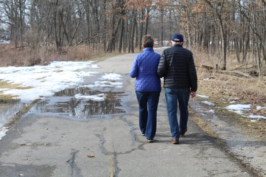 Older couple walking arm and arm at Miami Woods in Morton Grove, Illinois during a spring thaw on the North Branch Trail