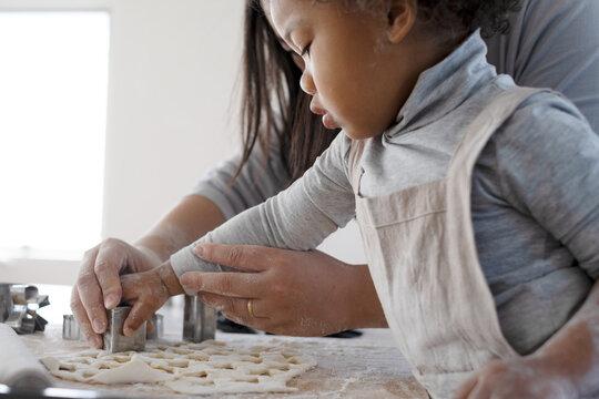 お母さんと一緒に初めてクッキーを作る女の子