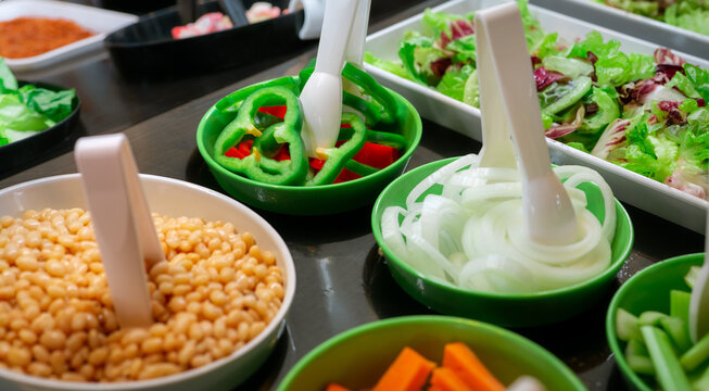 Salad bar buffet at restaurant. Fresh salad bar buffet for lunch or dinner. Healthy food. Green and red pepper and onions in green bowl on counter. Catering food. Banquet service. Vegetarian food.