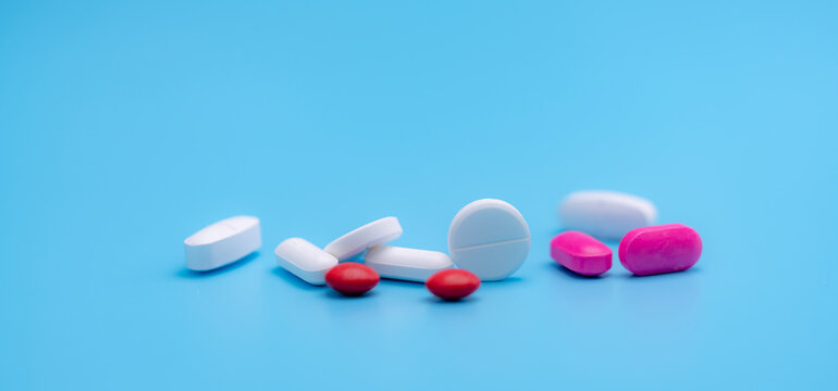 Pharmacy banner. White and pink tablets pills on blue background. Round and oval tablets. Painkiller medicine. Acetaminophen and ibuprofen tablets pills. Pharmaceutical industry. Painkiller tablets.