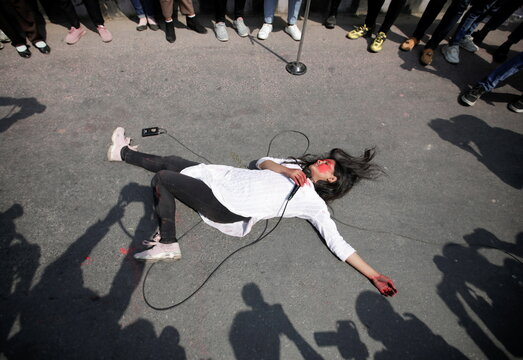 A woman performs an act against the growing incidents of violence on women during the International Women's Day in Kathmandu