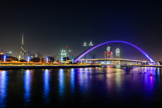 Night, cityscape of Dubai and the creek, tall buildings and waterfront, and illuminated bridge arch
