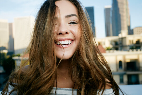 Portrait, a young mixed race woman on a city rooftop smiling, skyline behind her.