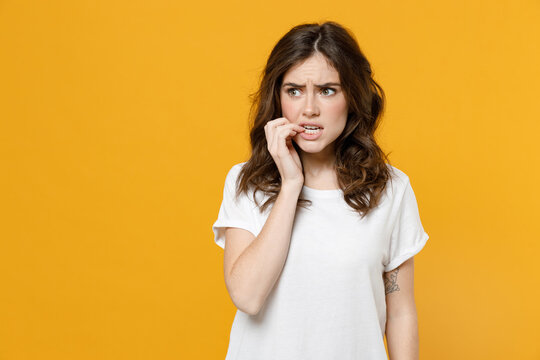 Young pensive thoughtful overthink mistaken troubled eueropean caucasian student woman 20s in white basic casual t-shirt look aside biting nails fingers isolated on yellow background studio portrait.