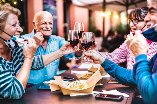 Senior people toasting wine at restaurant bar wearing open face masks - New normal life style concept with happy mature friends having fun together at garden party - Vivid filter with focus on glasses