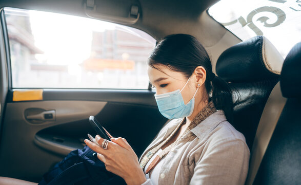 Young adult asian woman with face mask for public health in taxi car using mobile phone.