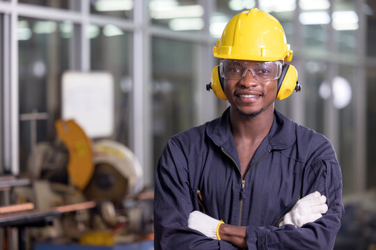 Portrait of cheerful black worker wearing protective headphones posing looking at camera and enjoying work at background factory
