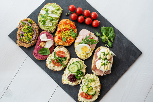 selection board of open sandwiches dips, spreads, cold cut meat, cheese, egg and salad