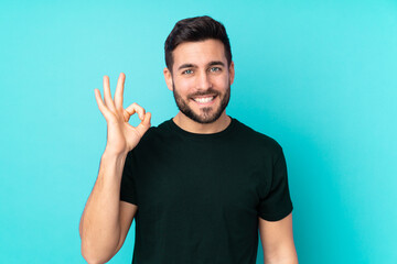 Fototapeta Caucasian handsome man isolated on blue background showing ok sign with fingers