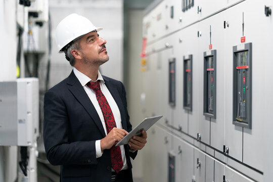 Portrait shot of senior engineer or management inspecting work in the electrical control room