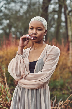 black woman posing in a forest during autumn