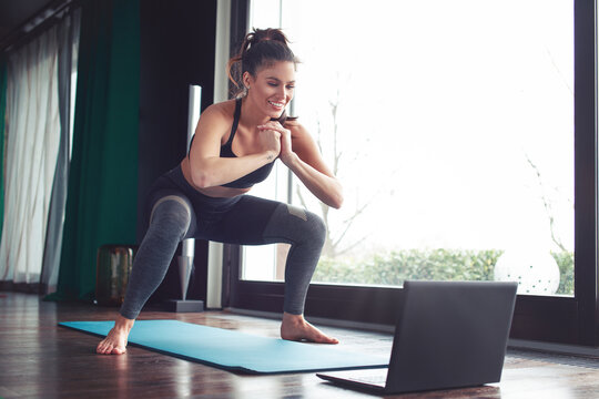 Happy young woman doing squat exercise from online tutorial