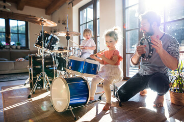 Fototapeta Portrait of small children with father indoors at home, playing drums.