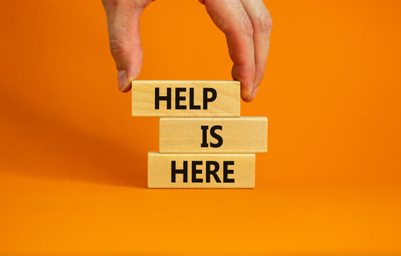 Help is here symbol. Wooden blocks with words 'Help is here' on beautiful orange background. Businessman hand. Business, support, help is here concept. Copy space.