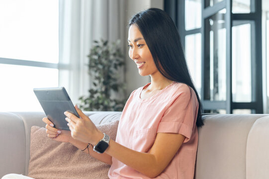 Young Asian mixed-race woman with long black hair sitting on the comfy couch smiling and holding digital tablet, talking with friend online on video call from home, watching comedy show or webinar