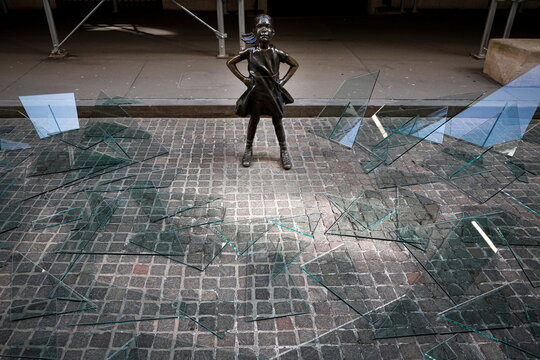 Broken glass ceiling installation surrounds The Fearless Girl statue in New York