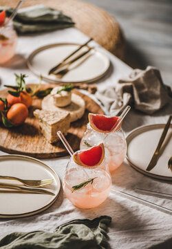 Cocktail party table setting. Grapefruit rosemary margaritas in glasses with straws, cheese fruit board, dinnerware, cutlery on linen tablecloth for romantic table setting and celebration