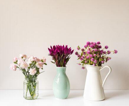 Cloose up of vases with pink and purple flowers incuding carnations, feathers, globe amaranths, on white table