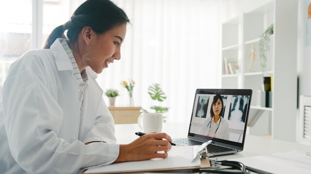 Young Asia lady doctor in white medical uniform using laptop talking video conference call with senior doctor at desk in health clinic or hospital. Social distancing, quarantine for corona virus.