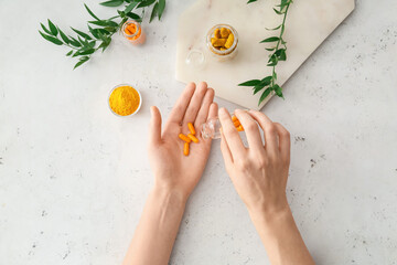 Fototapeta Female hands with turmeric pills, powder and roots on light background obraz