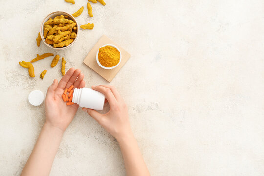 Female hands with turmeric pills, powder and roots on light background
