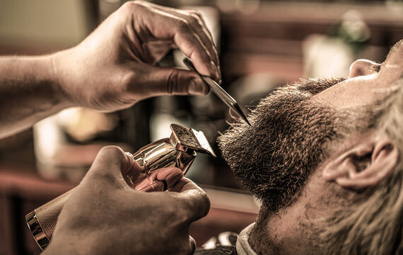 Man visiting hairstylist in barbershop. Barber works with a beard clipper. Hipster client getting haircut