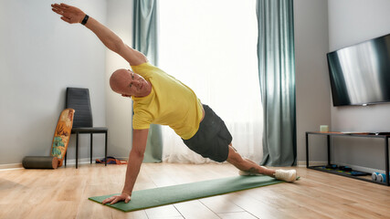 Stay active at any age. Mature man fitness instructor in sportswear standing in a plank on yoga mat at home and doing workout, exercising during self isolation