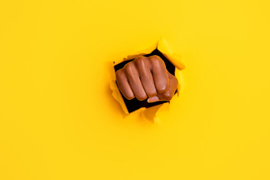 Photo of aggressive angry fighting fist hit big hole break through bright vibrant yellow color background