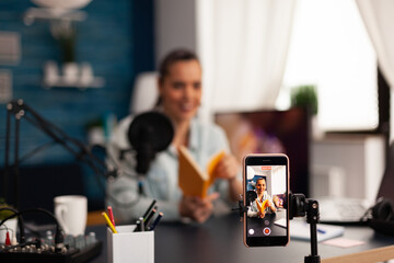 Obraz Vlogger holding book during podcast review on social media. Creative content creator influencer streaming live video, recording digital social media communication for her audience - fototapety do salonu