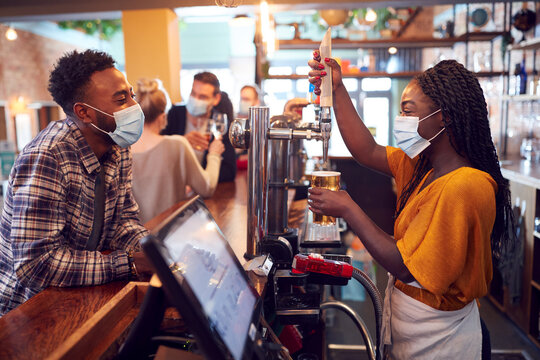 Female Bartender Wearing Face Mask Serving Male Customer With Beer During Health Pandemic
