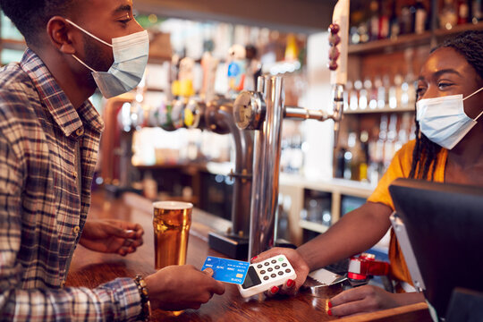 Male Customer Wearing Mask In Bar Making Contactless Payment For Drinks During Health Pandemic