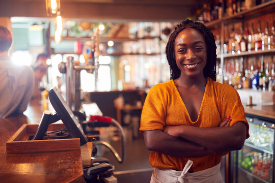 Portrait Of Smiling Female Bar Owner Standing Behind Counter