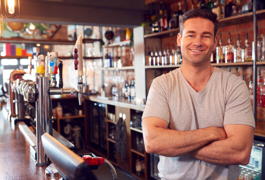 Portrait Of Smiling Male Bar Owner Standing Behind Counter