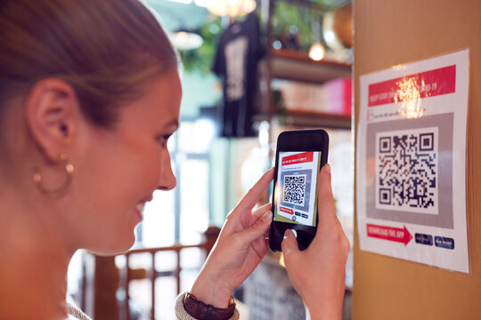 Woman With Mobile Phone Checking Into Venue Scanning QR Code During Health Pandemic