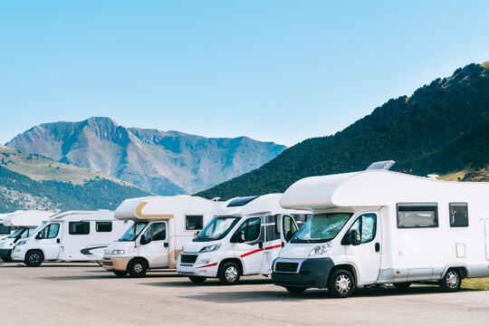Summer tourism with rv in the mountain. Campers parked in a row in a caravan parking area. Best option for travel feeling free. Motorhomes and campingcar.